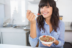 Attractive brunette eating bowl of cereal and fruit Stock Photos