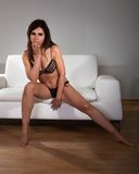 Young Woman In Lingerie Sitting On Couch Royalty Free Stock Photography