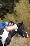 Attractive brunette female rider embracing her hor. Portrait of attractive brunette female rider embracing her horse and looking at camera Stock Photos
