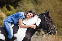 Attractive brunette female rider embracing her hor. Portrait of attractive brunette female rider embracing her horse and smiling Royalty Free Stock Photography