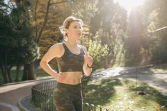 Attractive brunette female runner running in city park airpods bluetooth headphones earphones. Portrait of attractive brunette female runner running in city park royalty free stock image