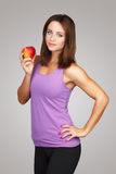 Attractive brunette fitness model with apple Royalty Free Stock Photography