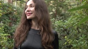Attractive brunette girl in black dress walking through tropical plants in greenhouse. 4K clip. Beautiful brunette girl walking through tropical plants in big stock video