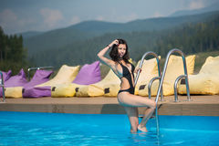 Attractive brunette girl in black swimsuit is posing in the swimming pool on mountain resort. On the background hills and forest in the distance Stock Image