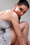 Attractive brunette girl close up. Attractive brunette girl posing in a silver mini dress Royalty Free Stock Image