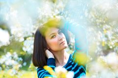 Attractive brunette girl close-up portrait through white flowers Royalty Free Stock Image
