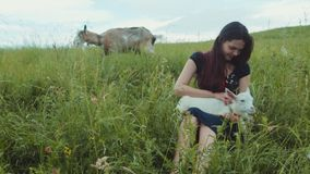 Attractive brunette girl from a countryside sitting in high green grass holding the white goat kid and stroking it. Nature lover, enjoying life. Cheerful mood stock video footage