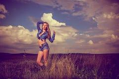 Attractive brunette girl in jeans, outdoor scene Stock Image