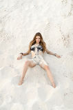 Attractive brunette  girl lies on the sand Royalty Free Stock Photos