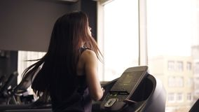 Attractive brunette girl with long hair in her 20`s wearing dryfit sportswear, running on treadmill. Indoors footage. Attractive brunette girl with long hair in stock footage