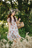 Attractive brunette girl with long hair wearing dress in floral print with wrath of wildflowers on head posing outdoor. Woman walk Royalty Free Stock Photos