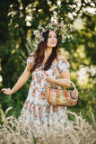 Attractive brunette girl with long hair wearing dress in floral print with wrath of wildflowers on head posing outdoor. Woman walk Stock Photos