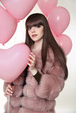 Attractive brunette girl with long healthy hair in fur fox coat. Posing with pink balloons  on studio white background Royalty Free Stock Photography