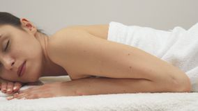 Girl lies on her stomach on the massage table stock photography