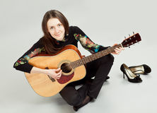 Attractive brunette girl playing guitar Stock Image