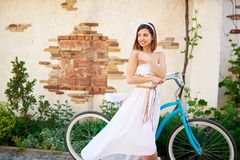 Attractive brunette girl posing near blue bike in front of old brick building. Attractive brunette girl in long white dress posing near blue bike looking to the Royalty Free Stock Photo