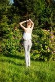 Attractive brunette girl posing outdoor. Beautiful young brunette girl posing over green summer garden in sunny day Stock Image
