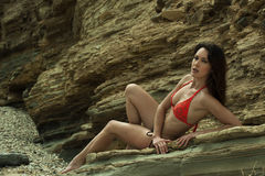 Attractive brunette girl posing sexy at the rocks. At Palos Verdes secret cove beach, CA Stock Images