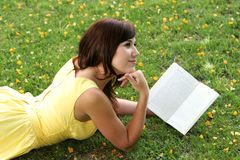 Attractive Brunette Girl Reading Outdoors Stock Photos