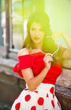 Attractive brunette girl with red blouse and sunglasses posing outdoor. Beautiful fashionable young woman with modern royalty free stock photography
