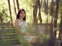 Attractive brunette girl sits in the park Royalty Free Stock Photography