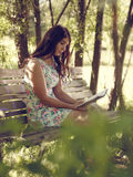 Attractive brunette girl sits in the park Royalty Free Stock Image