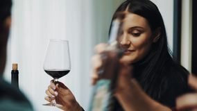 Attractive brunette girl smiling and clings wine glass at dinner table stock footage