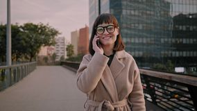Attractive brunette girl walks on urban streets. Cute girl in warm coat, round glasses walks around busy business neighbourhood in downtown reaches out for stock video