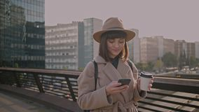 Attractive brunette girl walks on urban streets. Dreamy beautiful young woman chats with her friends using messaging apps on her futuristic smartphone surround stock video