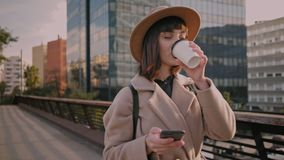 Attractive brunette girl walks on urban streets. Trendy student in fedora hta, round glasses and hipster backpack scrolls through her news feed on smartphone on stock video footage