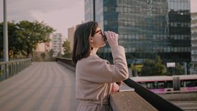Attractive brunette girl walks on urban streets. Young female student embraces the first sunlight on early morning before start of busy and full of classes and stock footage