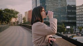 Attractive brunette girl walks on urban streets. Young trendy lawyer professional woman stands in the middle of buzzing street looks over the highway and stock video