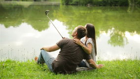 Attractive brunette and handsome man are taking photo of theirselves using selfie stick. Couple sitting near the lake on stock footage