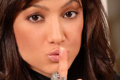 Attractive brunette with her finger to her lips royalty free stock images