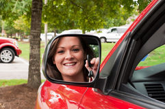 Attractive Brunette Holding Keys in Vehicle Mirror Stock Image