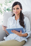 Attractive brunette holding tablet pc and credit card Stock Images