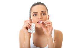 Attractive brunette holds some pills. Attractive young brunette takes some pills, isolated on white stock image
