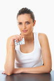 Attractive brunette holds some pills, isolated. Attractive young brunette holds some pills in her hand, isolated on white royalty free stock photography