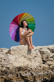 Attractive brunette with iridescent umbrella on wild rocky beach Royalty Free Stock Image