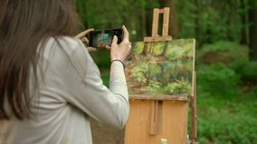 Attractive brunette lady paints a landscape in an open air in the forest and taking a photo. Back view. Woman artist takes a picture of her painted picture on stock video footage