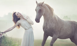 Attractive brunette lady and spotted horse stock photos