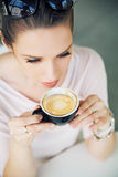 Attractive brunette lady taking a gulp of coffee royalty free stock photo