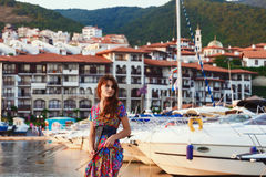 Attractive brunette in long colorful dress standing alone on the beach against the backdrop of yachts and town at sunset stock photos