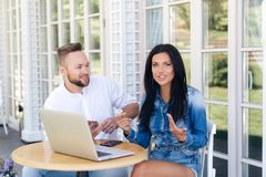 An attractive brunette with long hair talks about something to her friend behind the scenes, a guy with an interesting. Look at her. Friends are sitting in a royalty free stock photography