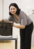 Attractive brunette looking in briefcase. Stock Photography