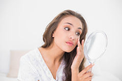 Attractive brunette looking closely at mirror Royalty Free Stock Image