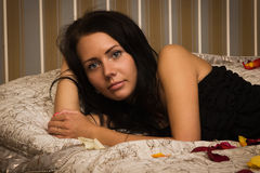 Attractive brunette lying on the bed Stock Image