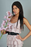 Attractive brunette model holding orchid flower Stock Photos