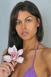 Portrait of attractive brunette model holding orchid flower Royalty Free Stock Photos