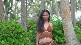 Attractive brunette model in original knitted bikini posing somewhere in tropics stock video footage